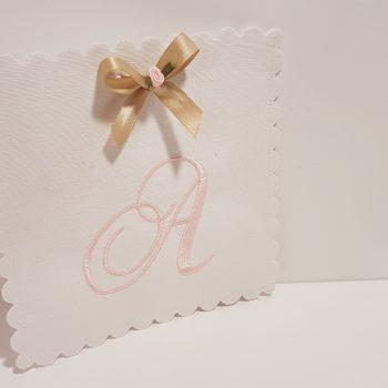 Προσκλητήριο λευκό λινό με κεντημένο μονόγραμμα ροζ .