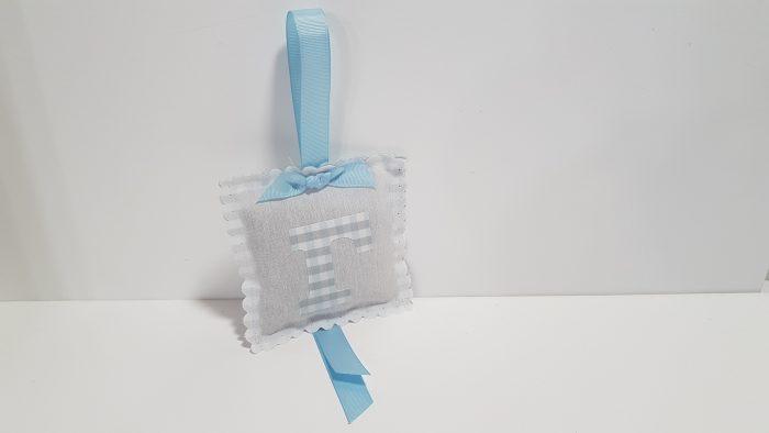 Μπομπονιέρα μαξιλαράκι με αρωματική λεβάντα και υφασμάτινο μονόγραμμα μπροστά.