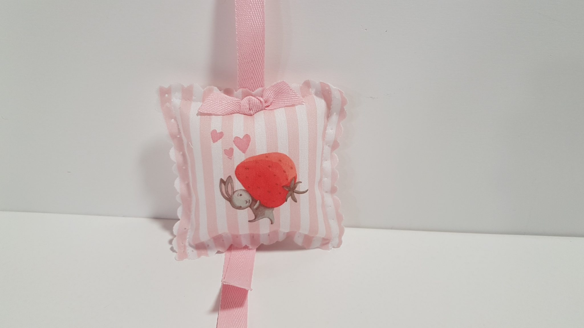 Μπομπονιέρα μαξιλαράκι φουσκωτό,΄θφασμα ριγέ και τυπωμένο λαγουδάκι με φράουλα.