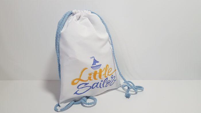 Σακίδιο παιδική μπομπονιέρα πίσω όψη σιέλ ύφασμα ,μπροστά τύπωμα ναυτικό θέμα .