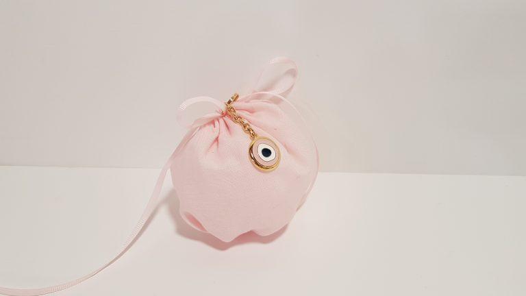 Μπομπονιέρα πουγκί ροζ με περαστή κορδέλα και μπρελόκ χρυσό μάτι.