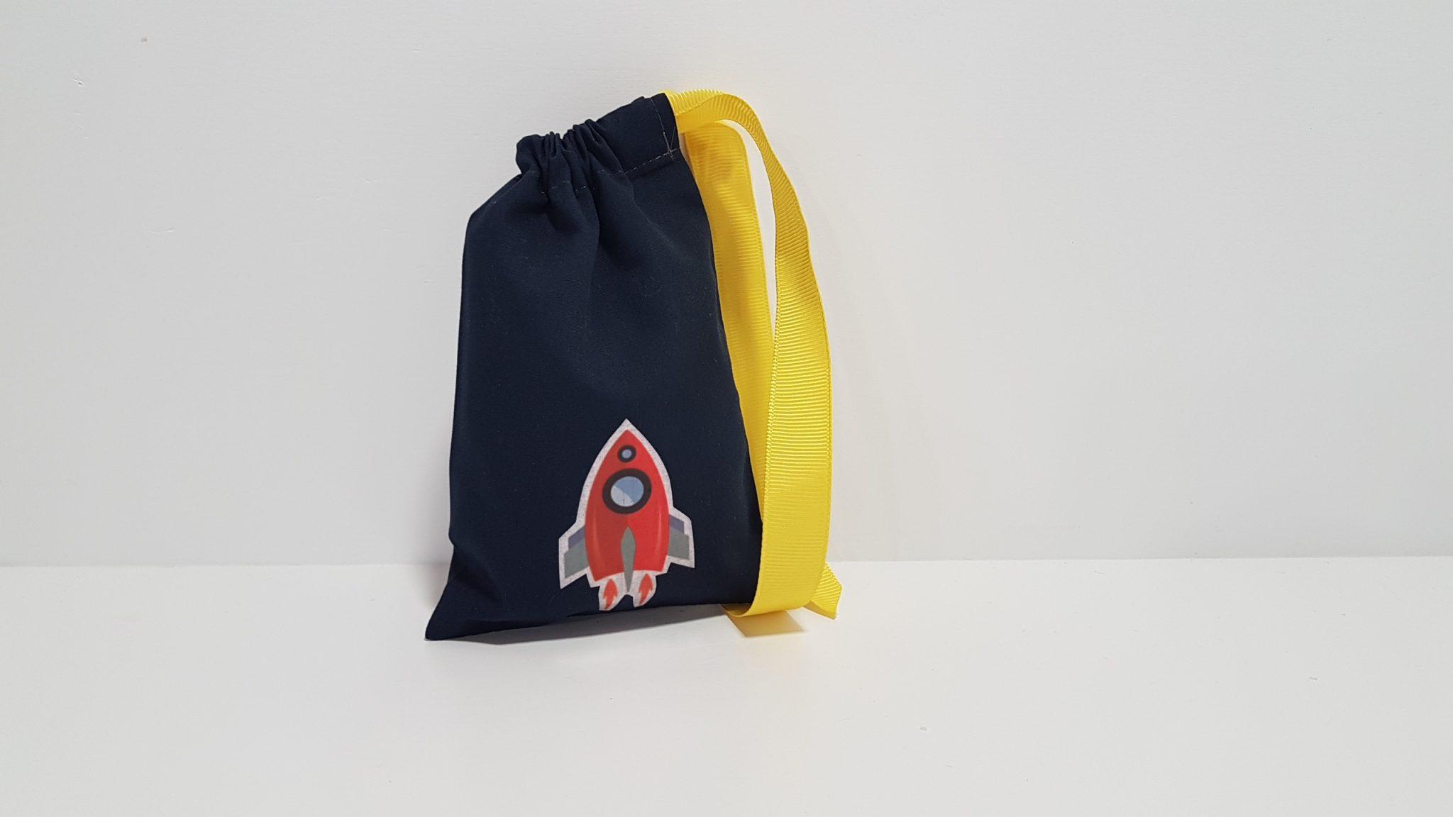 Μπομπονιέρα πουγκί με κόκκινο διαστημόπλοιο και περαστή κορδέλα.