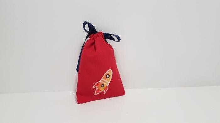 Μπομπονιέρα πουγκί με κίτρινο διαστημόπλοιο και περαστή κορδέλα.