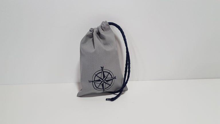Μπομπονιέρα πουγκί γκρι με απλικέ ναυτικό τιμόνι και περαστή κορδέλα.