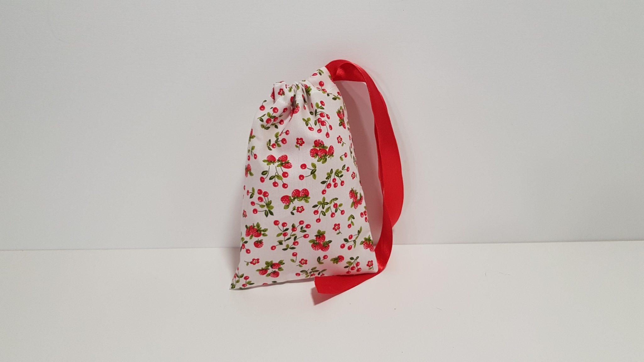 Μπομπονιέρα πουγκί με κερασάκια και φράουλες και περαστή κορδέλα.