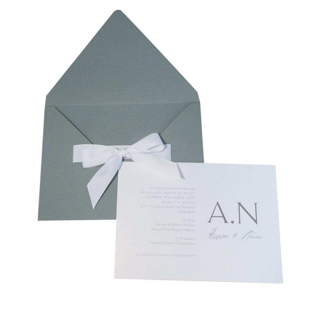Προσκλητήριο γάμου με λευκή κορδέλα σε γκρι φάκελο.