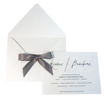 Λευκό προσκλητήριο γάμου με γκρι κορδέλα στον φάκελο.